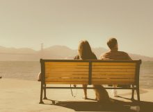 couple sitting on bench resolving conflict in marriage
